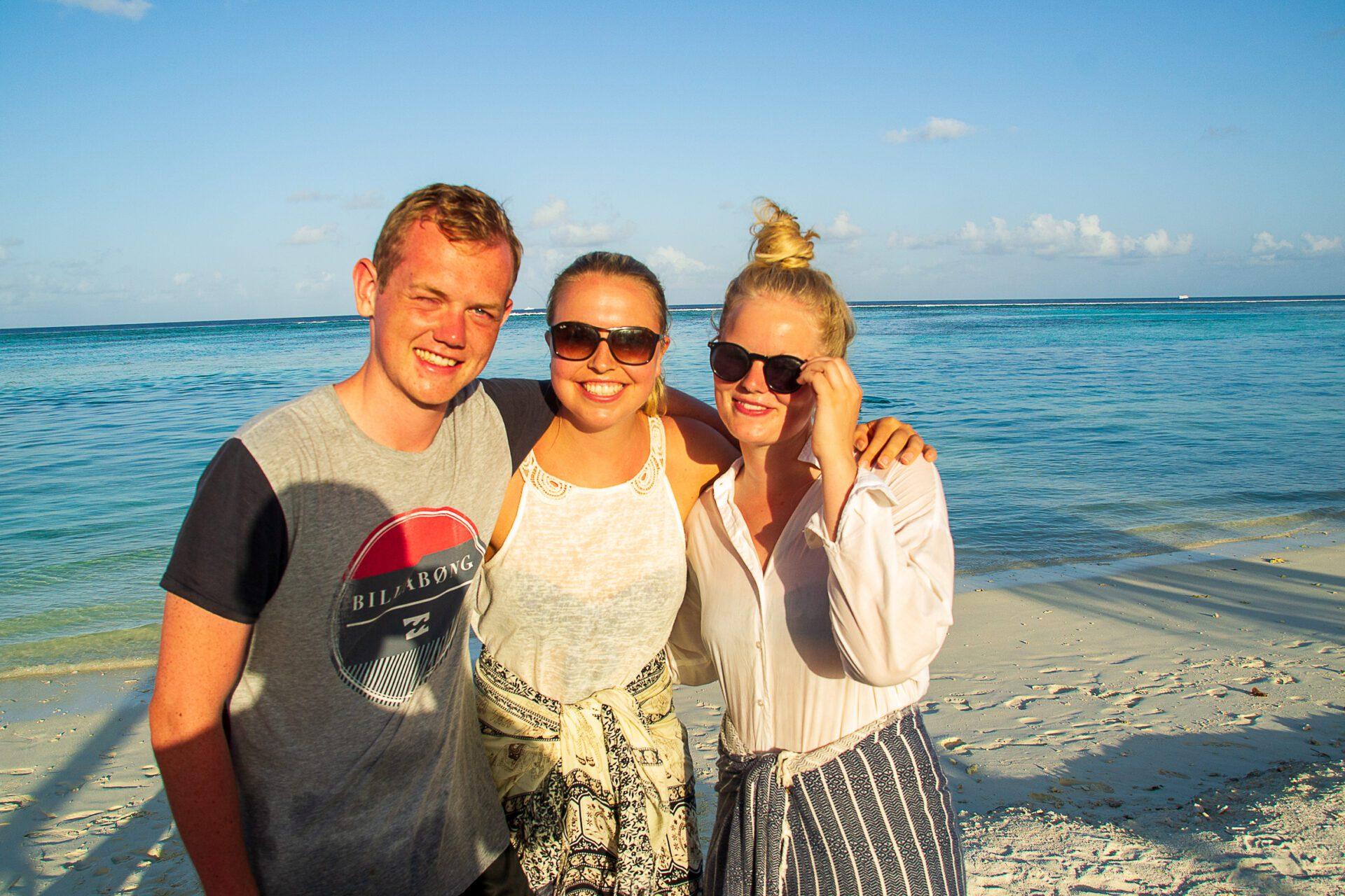 Smilende backpacker på strand på Maldiverne i Solskin