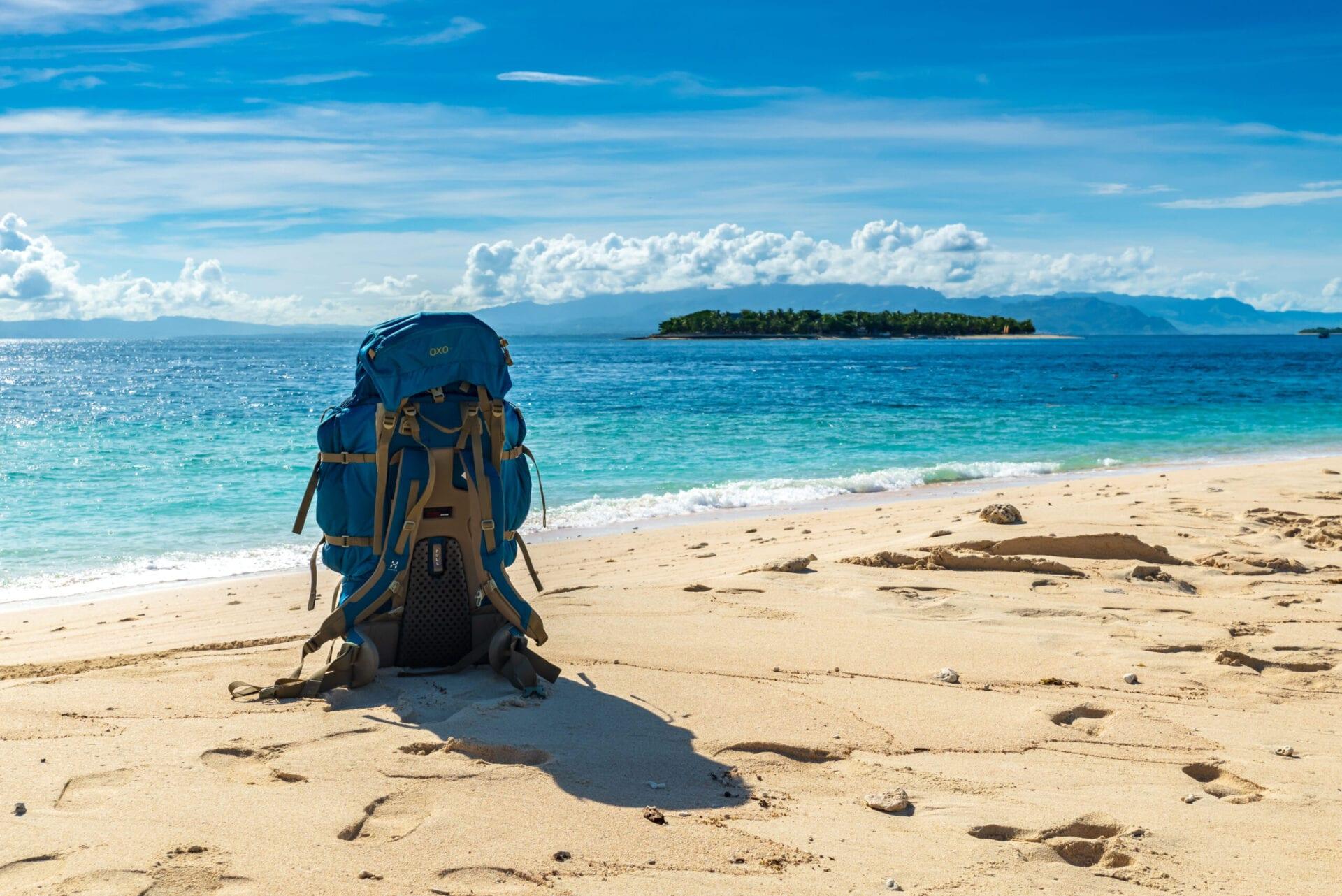 Backpack står alene på strand i solskin på Fiji